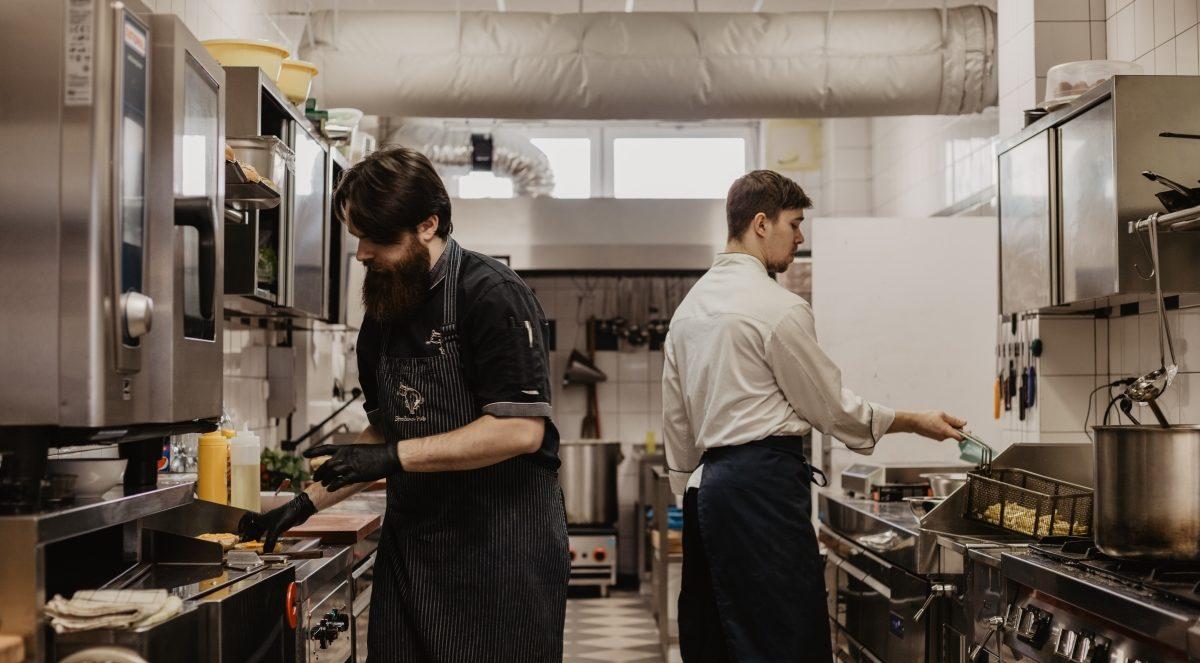 Dva kuchaři připravují jídlo v kuchyni.