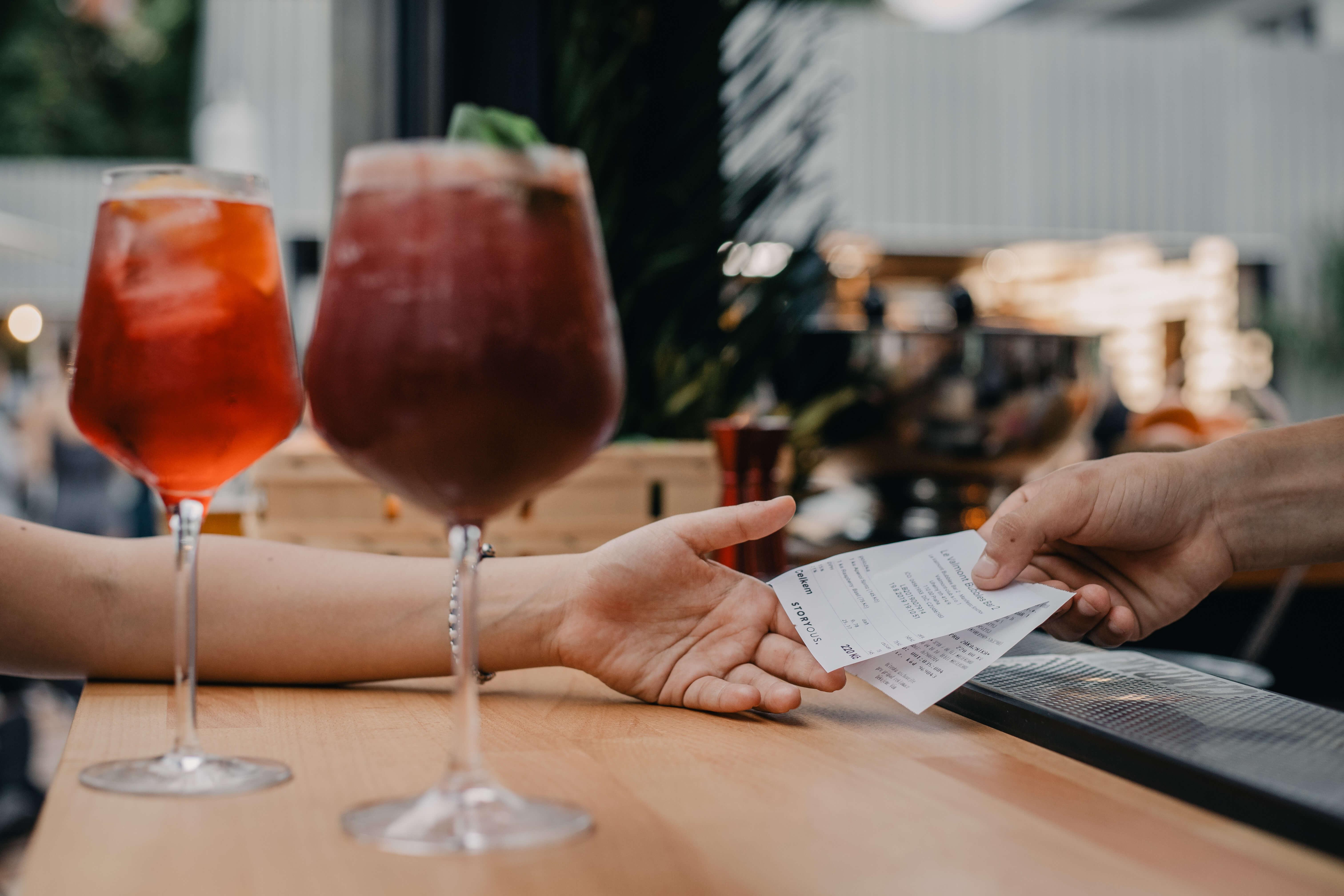 Zákazník na baru dostává účtenku.